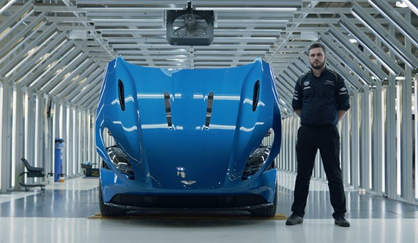 Male manufacturing engineering apprentice with blue Aston Martin